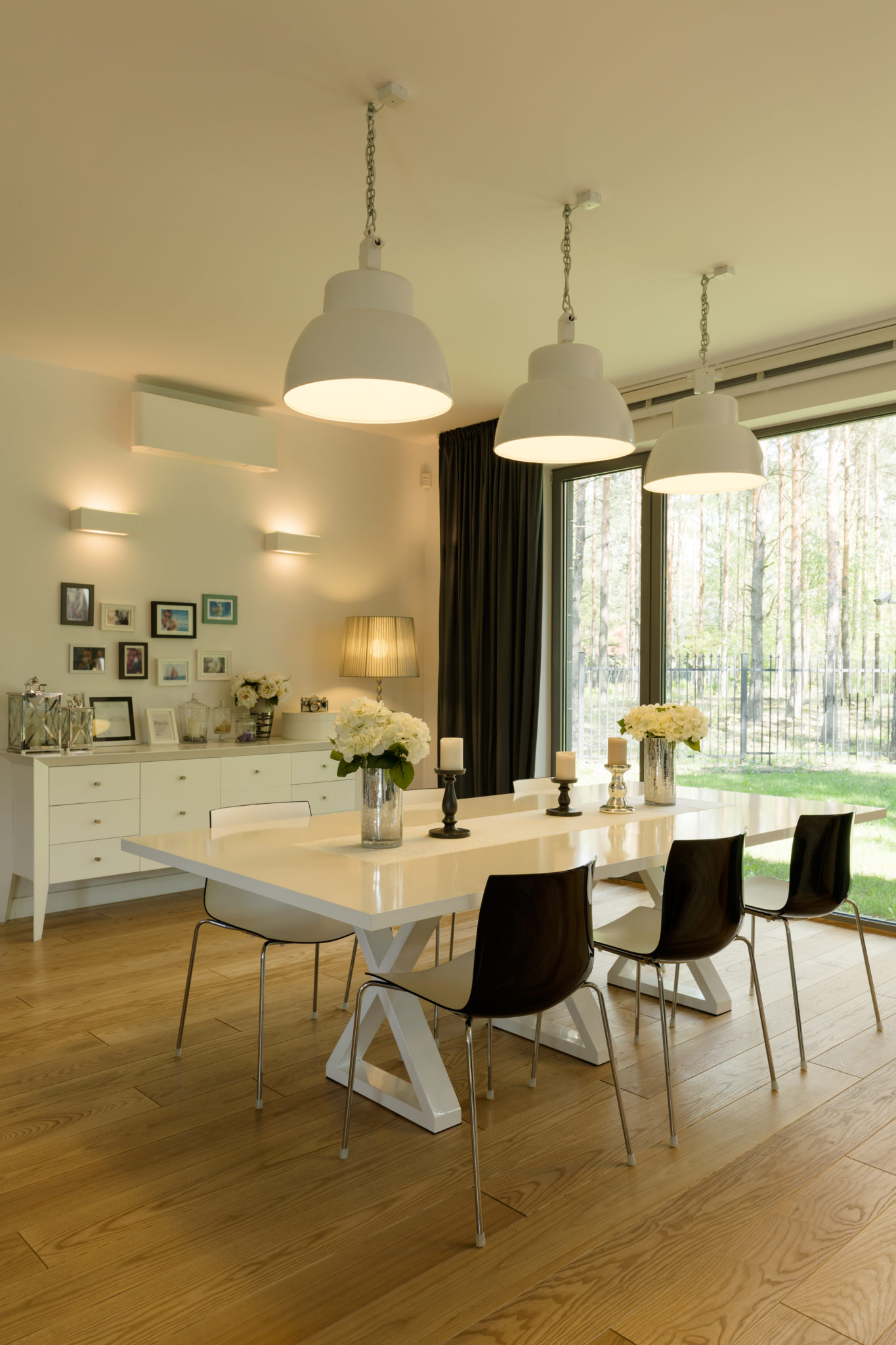 Spacious light dining room with wooden parquet and table