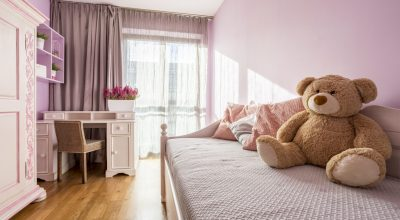 Teenage girl's pink bedroom with big teddy bear on a bed