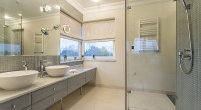 Spacious white bathroom with glass door shower and two sinks